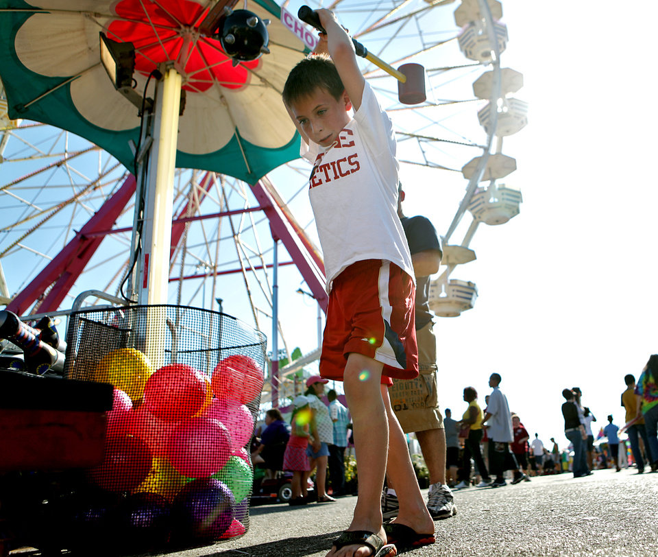 Photo - Chase Ogletree, age 9, of Walters, Okla., tries a game on the Midway at the 2009 Oklahoma State Fair at State Fair Park in Oklahoma City on Sunday, Sept. 27, 2009.  By John Clanton, The Oklahoman
