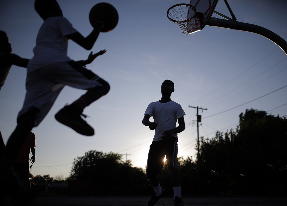 Photo -  Youths play basketball during the Midnight Basketball outreach at Christ Temple Community Church, 2717 N Kelley in Oklahoma City. Photo by Sarah Phipps, The    SARAH PHIPPS