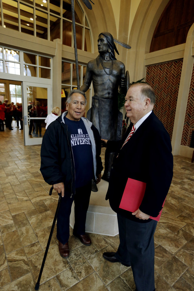 "Photo - Artist Kelly Haney and OU President David Boren pause at the entrance to Headington Hall with Haney's sculpture ""The Guardian,"" before the dedication of Headington Hall on the campus of the University of Oklahoma (OU) on Saturday, Nov. 16, 2013 in Norman, Okla.  Photo by Steve Sisney, The Oklahoman"