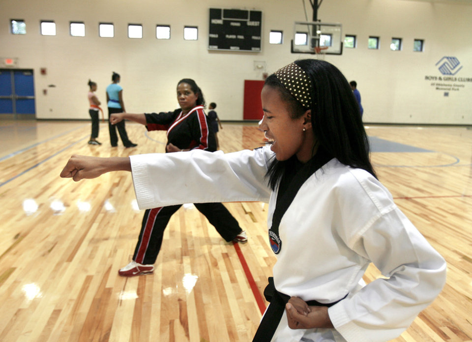 Photo - Lauren Morrison, front, and her mother, Cherry, practice together at the Memorial Park Boys & Girls Club on N Western Avenue in Oklahoma City. Lauren has overcome the challenges of cerebral palsy by becoming a black belt and winning world championships.