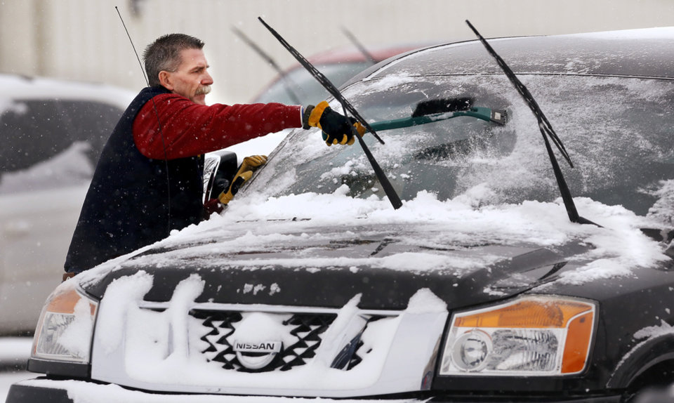 A man scrapes ice and snow from his car\'s windshield after Sunday services at a church in Midwest City. Snow began falling in central Oklahoma around 7 Sunday morning, Feb. 2, 2014. Photo by Jim Beckel, The Oklahoman