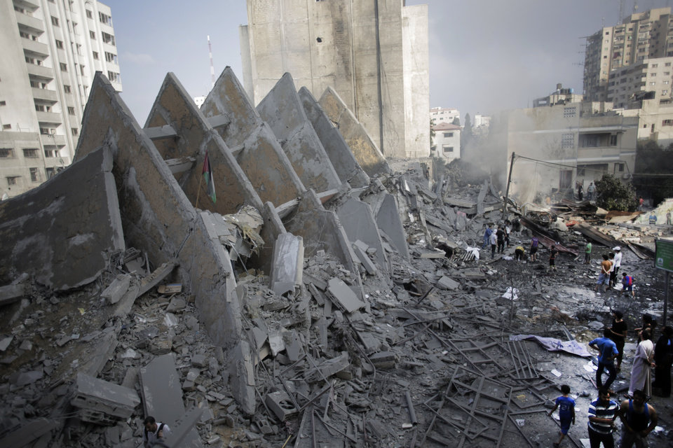 Photo - Palestinians inspect the rubble of the destroyed 15-story Basha Tower following early morning Israeli airstrikes in Gaza City, Tuesday, Aug. 26, 2014. Israel bombed two Gaza City high-rises with dozens of homes and shops Tuesday, collapsing the 15-story Basha Tower and severely damaging the Italian Complex in a further escalation in seven weeks of cross-border fighting with Hamas. Both buildings were evacuated after receiving warnings of impending strikes. (AP Photo/Khalil Hamra)