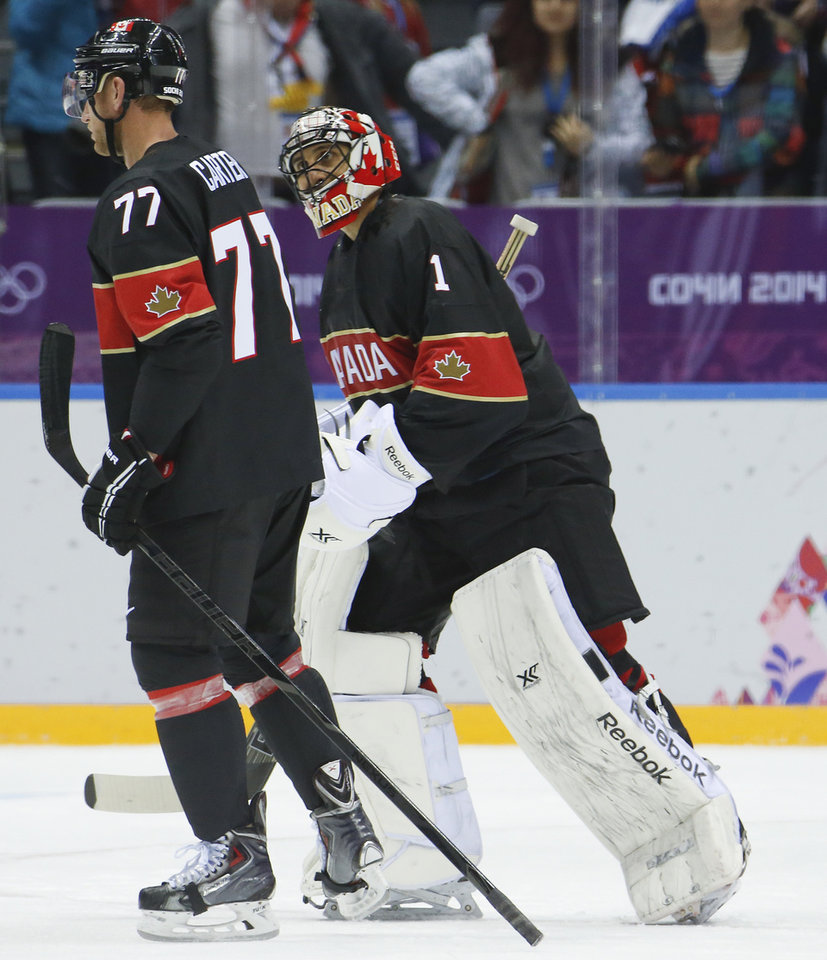 Photo - =Canada forward Jeff Carter, left, and Canada goaltender Roberto Luongo skate off the ice together after beating Austria 6-0 in a men's ice hockey game at the 2014 Winter Olympics, Friday, Feb. 14, 2014, in Sochi, Russia. Carter scored a hat trick in the game and Luongo recorded a shutout. (AP Photo/Mark Humphrey)