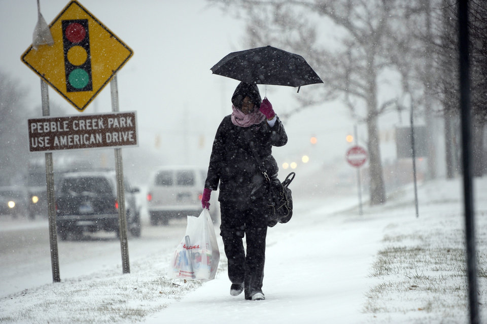 Photo - Brittany Hale, of Southfield, makes her way down Franklin Road in Southfield, Mich., Wednesday afternoon, Dec. 26, 2012. (AP Photo/The Detroit News, David Guralnick)
