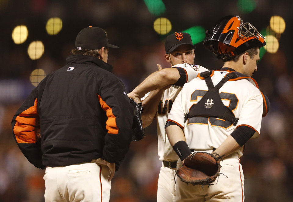 Photo - San Francisco Giants pitcher George Kontos, center, receives a visit on the mound from catcher Buster Posey, right, and pitching coach Dave Righetti during the seventh inning of a baseball game against the Washington Nationals, Monday, June 9, 2014, in San Francisco. (AP Photo/Beck Diefenbach)
