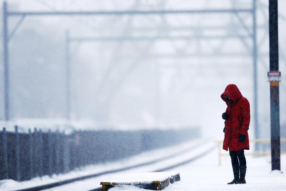 Photo - A morning commuter waits on a train during a winter snowstorm Monday, March 3, 2014, in Philadelphia. (AP Photo/Matt Rourke)