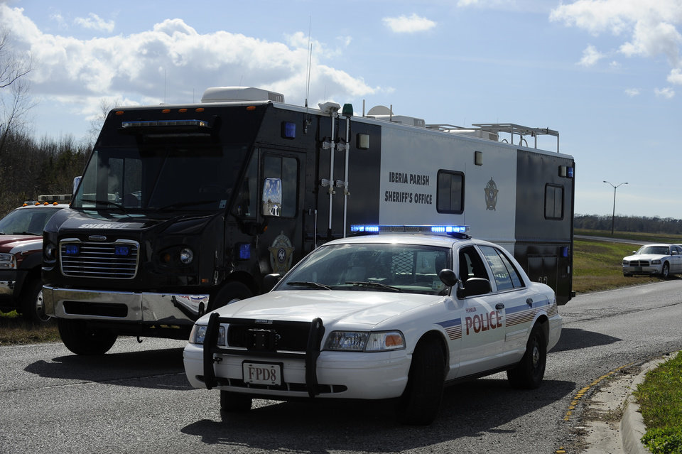Photo - An Iberia Parish Sheriff's Office command post is driven to the scene of a shooting Saturday, Jan. 26, 2013 in Charenton, La.  Police on Saturday arrested a man suspected of fatally shooting a police officer and critically wounding two sheriff's deputies after setting a deadly fire at a mobile home near a south Louisiana casino. (AP Photo/The Daily Iberian, Lee Ball)