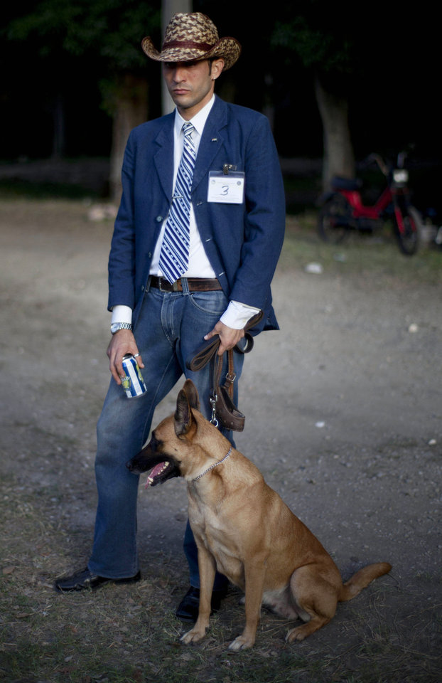 In this Nov. 23, 2012 photo, a man watches the competition with his German shepherd at the Fall Canine Expo in Havana, Cuba. Hundreds of people from all over Cuba and several other countries came for the four-day competition to show off their shih tzus, beagles, schnauzers and cocker spaniels that are the annual Fall Canine Expo's star attractions. (AP Photo/Ramon Espinosa)