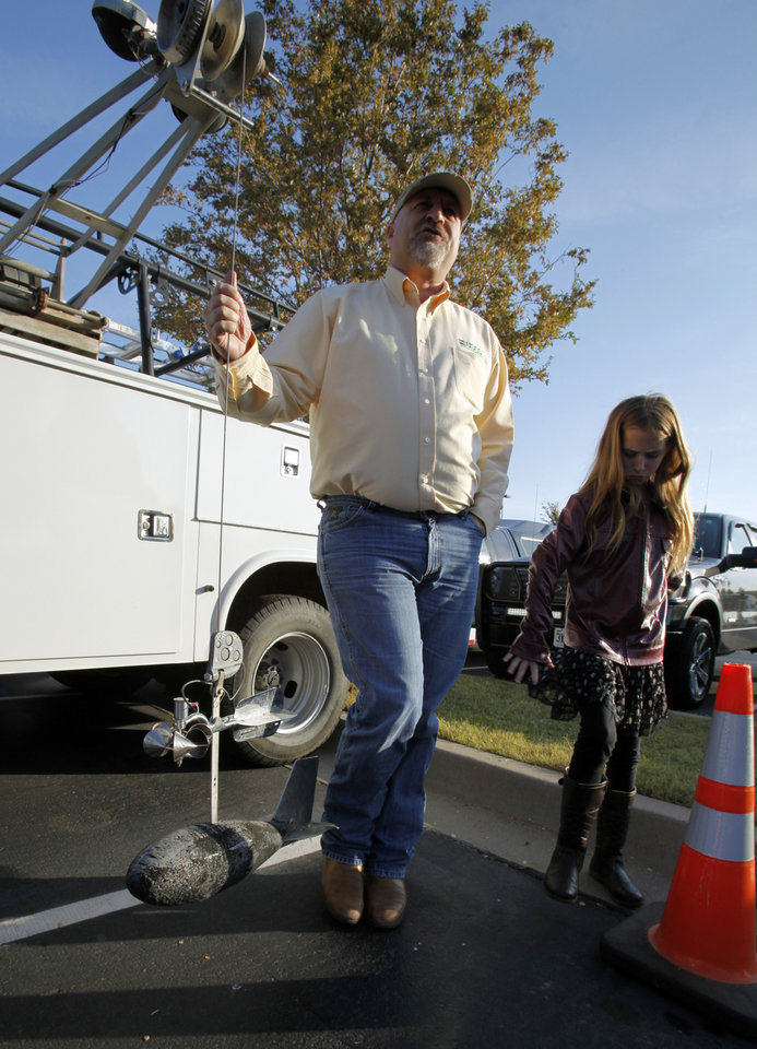 James Hanlon, hydrologist with the USGS, shows a water current meter at the National Weather Center Weather Festival, on Saturday, Nov. 3, 2012.  Beside him is his daughter Jillian, 9.  Photo by Steve Sisney, The Oklahoman