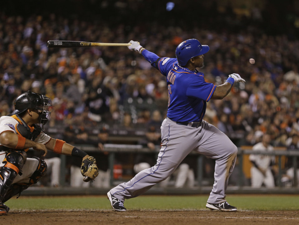 New York Mets' Marlon Byrd hits a grand slam home run to left field off San Francisco Giants relief pitcher Jake Dunning in the eighth inning of their baseball game Tuesday, July 9, 2013, in San Francisco. At left is San Francisco Giants catcher Guillermo Quiroz. (AP Photo/Eric Risberg)