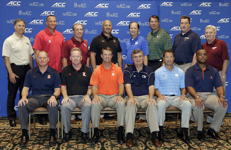 Photo - Atlantic Coast Conference football coaches pose for a group photo during the ACC Football kickoff in Greensboro, N.C., Monday, July 21, 2014. The coaches are, back row from left: Wake Forest's Dave Clawson, North Carolina State's Dave Doeren, Florida State's Jimbo Fisher, Boston College's Steve Addazio, Duke's David Cutcliffe, Miami's Al Golden, Pittsburgh's Paul Chryst, and Virginia Tech's Frank Beamer. Front row, from left are: Syracuse's Scott Shafer, Louisville's Bobby Petrino, Clemson's Dabo Swinney, Georgia Tech's Paul Johnson, North Carolina's Larry Fedora, and Virginia's Mike London.(AP Photo/Chuck Burton)