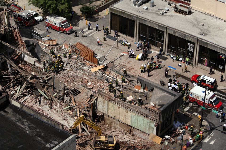 Photo - Rescue personnel work the scene of a building collapse in downtown Philadelphia, Wednesday, June 5, 2013.  A four-story building being demolished collapsed Wednesday on the edge of downtown, injuring 12 people and trapping two others, the fire commissioner said. Rescue crews were trying to extricate the two people who were trapped, and the dozen people who were injured were taken to hospitals with minor injuries, according to city Fire Commissioner Lloyd Ayers. (AP Photo/Jacqueline Larma)