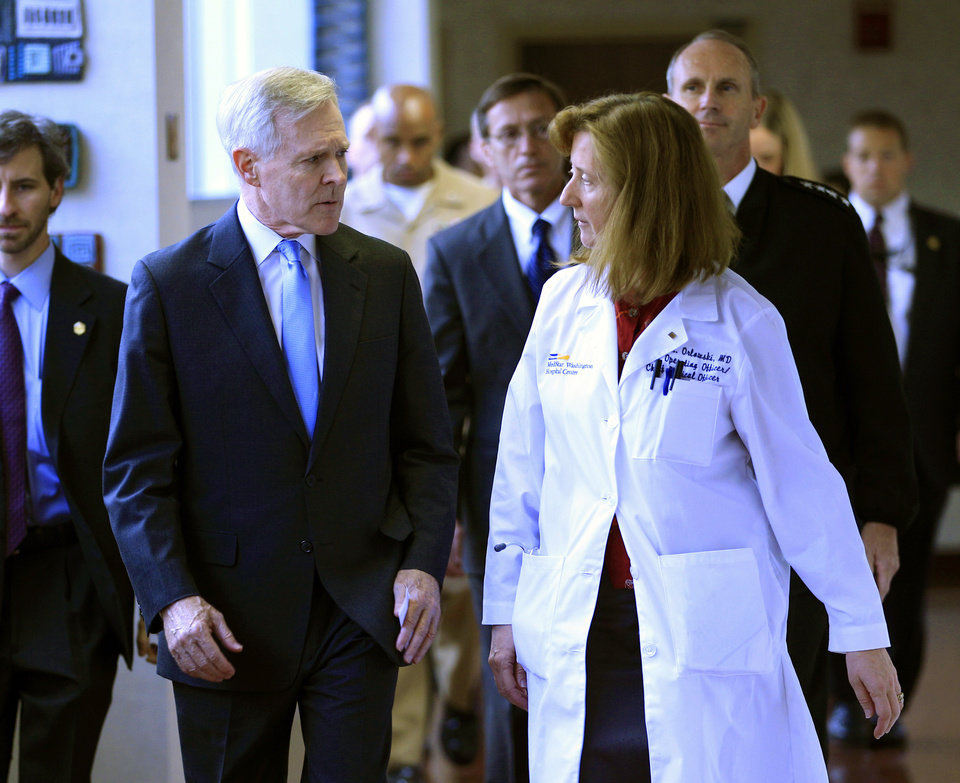 Photo - Secretary of the Navy Ray Mabus speaks with Dr. Janis M. Orlowski as they walk in the corridor at Washington Hospital Center, in Washington, on Monday, Sept. 16, 2013, after visiting the people injured in the shooting at the Washington Navy Yard. At least one gunman launched an attack inside the Washington Navy Yard, spraying gunfire on office workers in the cafeteria and in the hallways at the heavily secured military installation in the heart of the nation's capital, authorities said. (AP Photo/Jose Luis Magana)