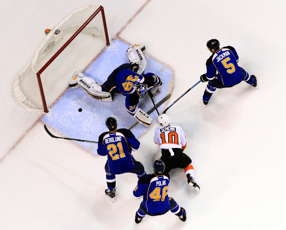 Photo - Philadelphia Flyers' Brayden Schenn (10) watches along with St. Louis Blues' Patrik Berglund (21), of Sweden, Roman Polak (46), of the Czech Republic, and Barret Jackman (5) as Blues goalie Ryan Miller (39) makes a save during the first period of an NHL hockey game Tuesday, April 1, 2014, in St. Louis. (AP Photo/Jeff Roberson)