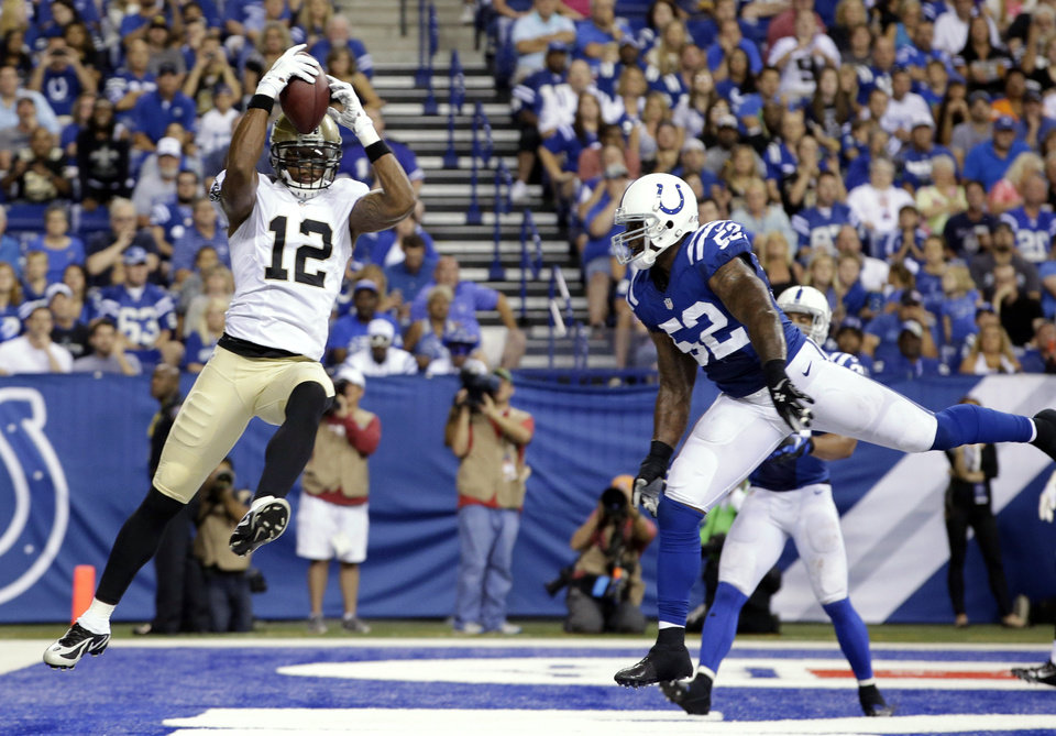 Photo - New Orleans Saints wide receiver Marques Colston (12) makes a catch for a touchdown in front of Indianapolis Colts inside linebacker D'Qwell Jackson during the first half of an NFL preseason football game in Indianapolis, Saturday, Aug. 23, 2014. (AP Photo/AJ Mast)