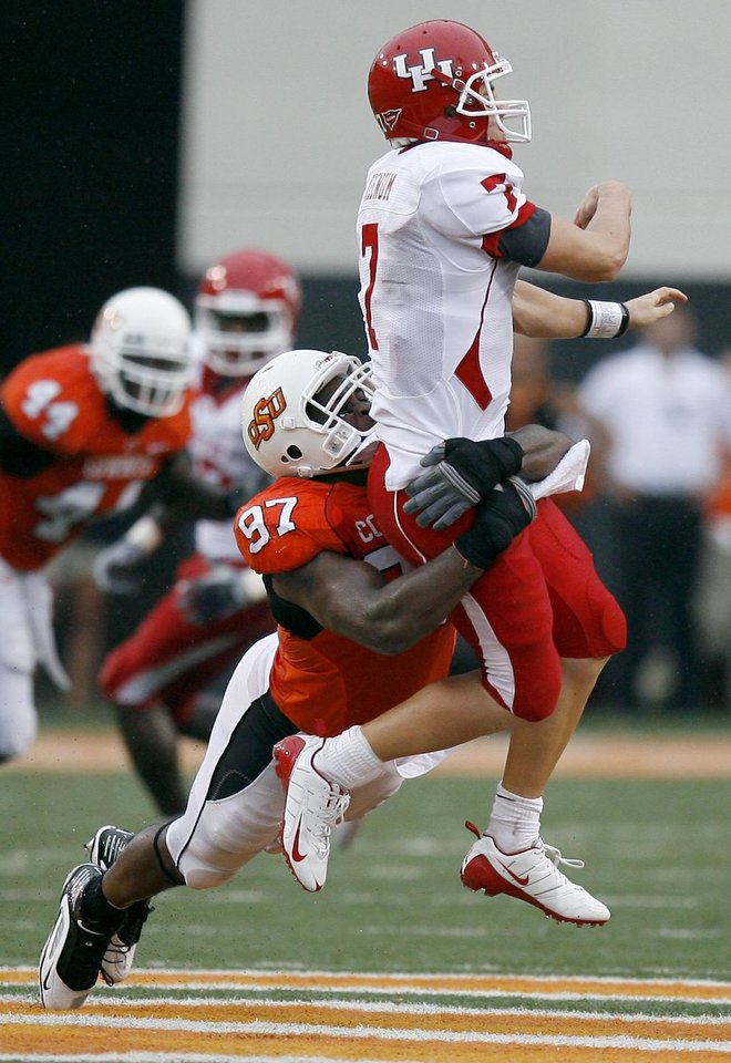 Photo - OSU's Jermiah Price (97) tackles Case Keenum (7) during the college football game between the University of Houston (UH) Cougars and the Oklahoma State University (OSU) Cowboys at Boone Pickens Stadium in Stillwater, Okla., Saturday, September 12, 2009. Photo by Sarah Phipps, The Oklahoman ORG XMIT: KOD