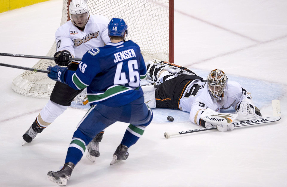 Photo - Anaheim Ducks Corey Perry (10) tries to clear Vancouver Canucks Nicklas Jensen (46) from in front of Anaheim Ducks goalie John Gibson (36) during the third period of NHL action in Vancouver, Monday, April 7, 2014. (AP Photo/The Canadian Press, Jonathan Hayward)