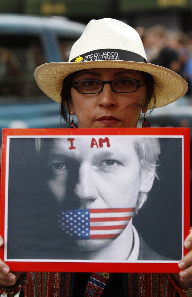 Photo -   A supporter of WikiLeaks founder Julian Assange holds up a placard outside the Ecuadorian Embassy in central London, London, Thursday, Aug. 16, 2012. WikiLeaks founder Julian Assange entered the embassy in June in an attempt to gain political asylum to prevent him from being extradited to Sweden, where he faces allegations of sex crimes, which he denies. WikiLeaks chief Julian Assange was granted political asylum by Ecuador on Thursday, setting up a standoff with the British government, which has vowed to block his exit from the country. (AP Photo/Sang Tan)