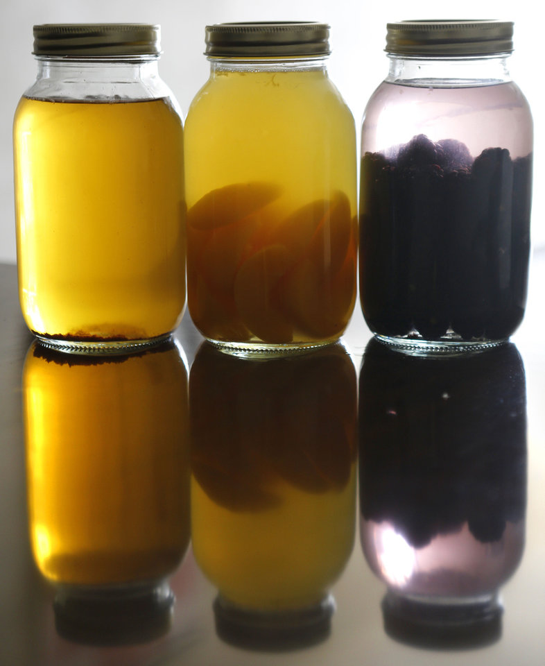Photo - Twister Distillery will soon introduce three flavors of moonshine: (from left) apple pie, Stratford peach and blackberry.  Steve Gooch - The Oklahoman