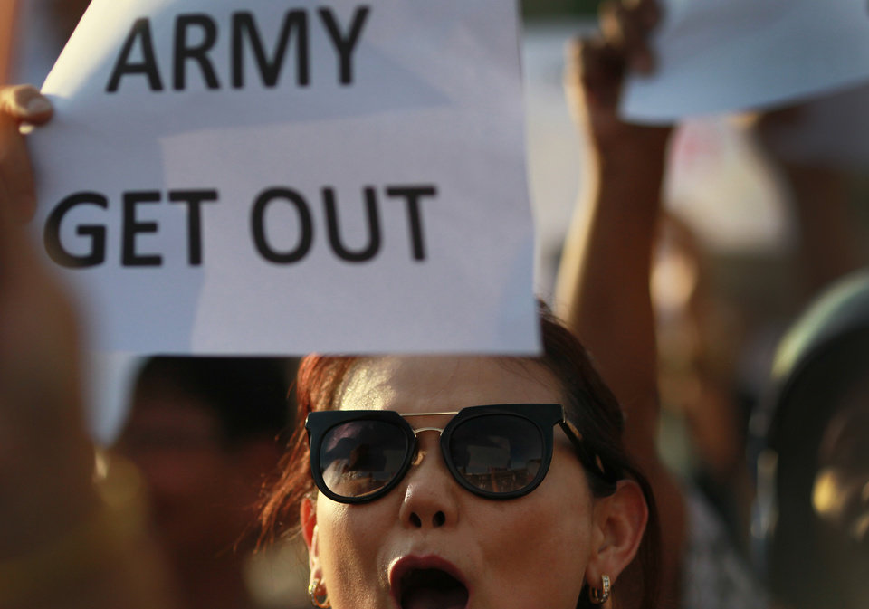 Photo - An anti-coup protester holds a banner and shouts during a demonstration at the Victory Monumet in Bangkok, Thailand Saturday, May 24, 2014. Thailand's coup leaders said Saturday that they would keep former Prime Minister Yingluck Shinawatra, Cabinet members and anti-government protest leaders detained for up to a week to give them