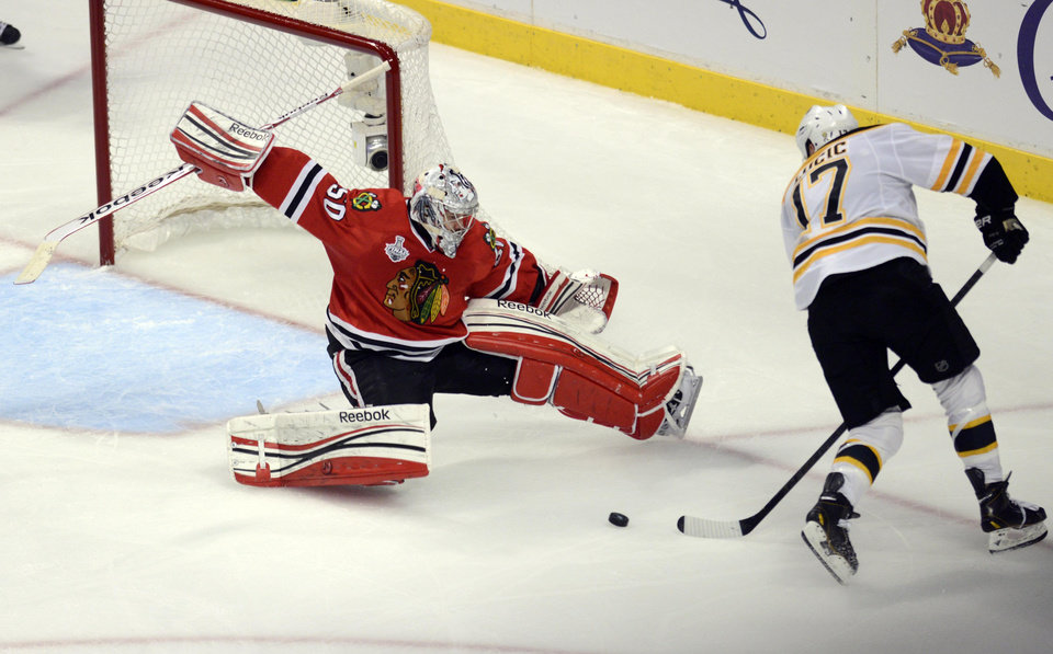 Chicago Blackhawks goalie Corey Crawford blocks a shot by Boston Bruins left wing Milan Lucic late in the third period during Game 1 in the NHL Stanley Cup Final hockey series , Wednesday, June 12, 2013, in Chicago. The Blackhawks won 4-3. (AP Photo/Daily Herald,  John Starks)