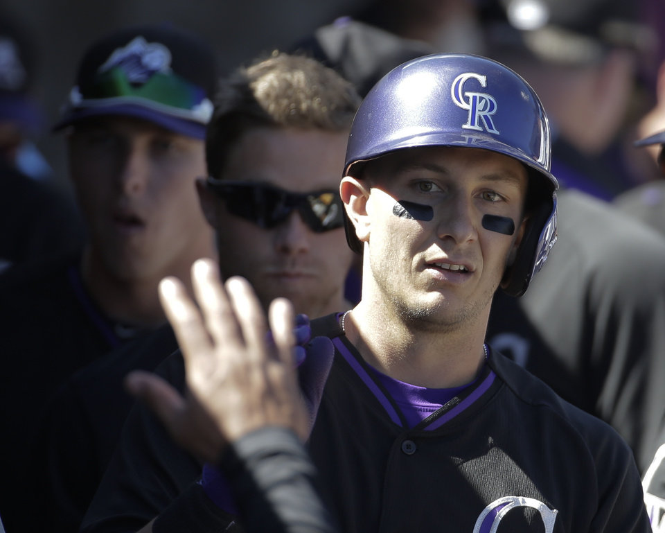 Photo - Colorado Rockies' Troy Tulowitzki celebrates in the dugout after scoring during the first inning of a spring training baseball game against the Oakland Athletics in Scottsdale, Ariz., Saturday, March 8, 2014. (AP Photo/Chris Carlson)