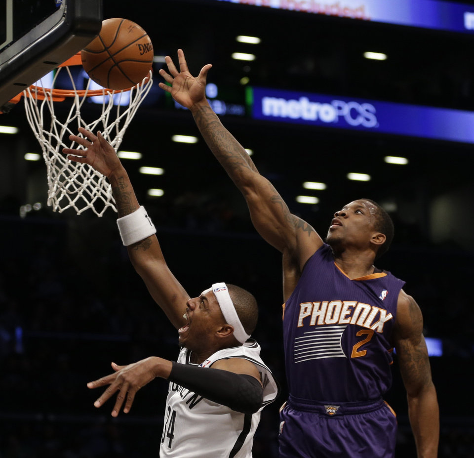Photo - Brooklyn Nets's Paul Pierce, left, puts up a shot while Phoenix Suns' Eric Bledsoe defends during the first half of the NBA basketball game at the Barclays Center Monday, March 17, 2014 in New York. (AP Photo/Seth Wenig)