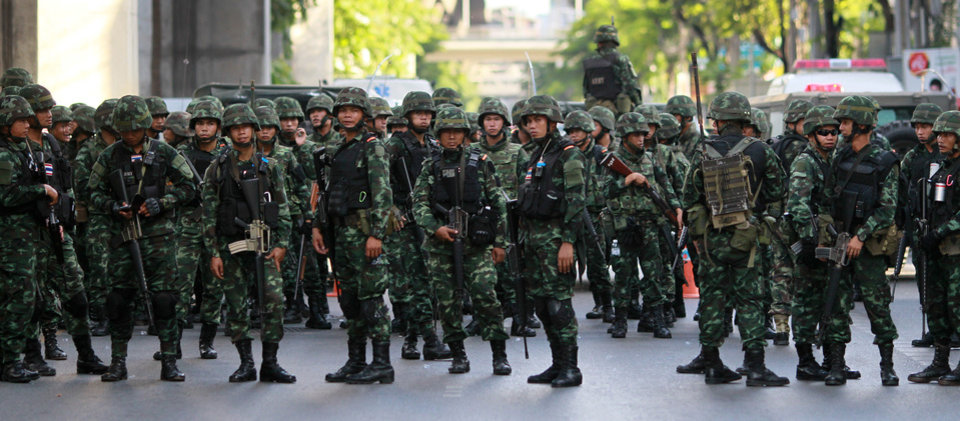 Photo - Thai soldiers  wait near the Victory Monument during an anti-coup demonstration in Bangkok, Thailand Saturday, May 24, 2014. Thailand's coup leaders said Saturday that they would keep former Prime Minister Yingluck Shinawatra, Cabinet members and anti-government protest leaders detained for up to a week to give them