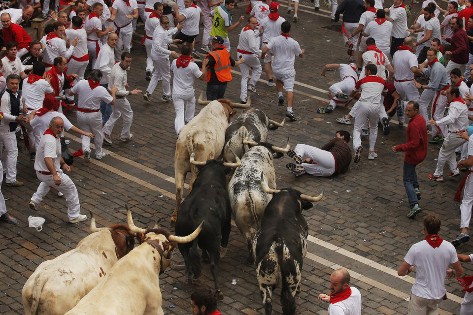 Photo - Torrestrella fighting bulls and revelers run during the running of the bulls of the San Fermin festival, in Pamplona, Spain, Monday, July 7, 2014. Revelers from around the world arrive here to take part in the eight-day event glorified by Ernest Hemingway's 1926 novel