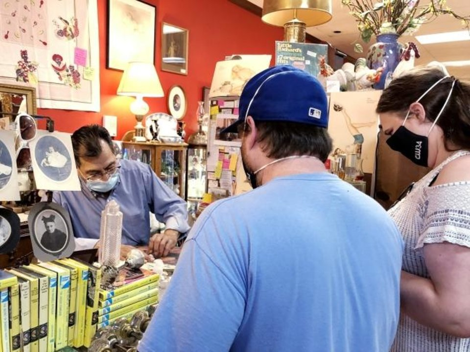 Photo -  Art Aguirre, owner of Magnolia Antique Mall in Guthrie, helps customers on Aug. 31 in his store. [Oklahoman Archive Photo]