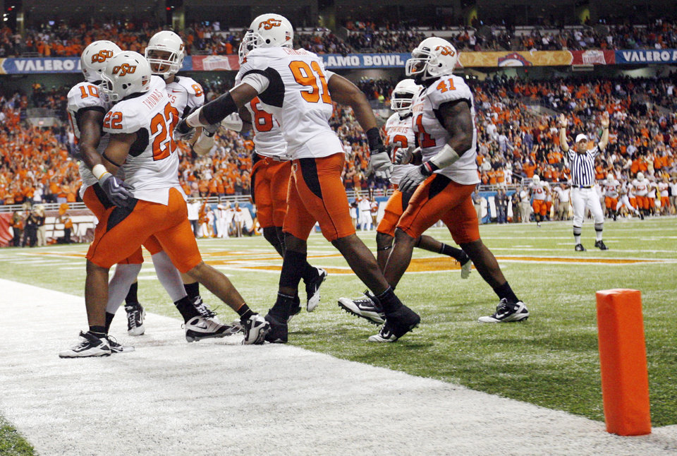 Photo - OSU players celebrate with Markelle Martin (10) after Martin returned an interception for a touchdown in the second quarter during the Valero Alamo Bowl college football game between the Oklahoma State University Cowboys (OSU) and the University of Arizona Wildcats at the Alamodome in San Antonio, Texas, Wednesday, December 29, 2010. Photo by Nate Billings, The Oklahoman