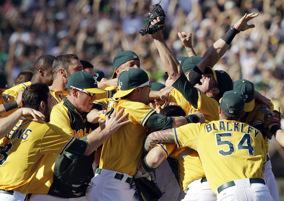 Photo -   Oakland Athletics relief pitcher Grant Balfour, third right looking, up celebrates with teammates after their 12-5 win over the Texas Rangers in a baseball game, Wednesday, Oct. 3, 2012 in Oakland, Calif. The A's clinch the AL West title with the win. (AP Photo/Ben Margot)