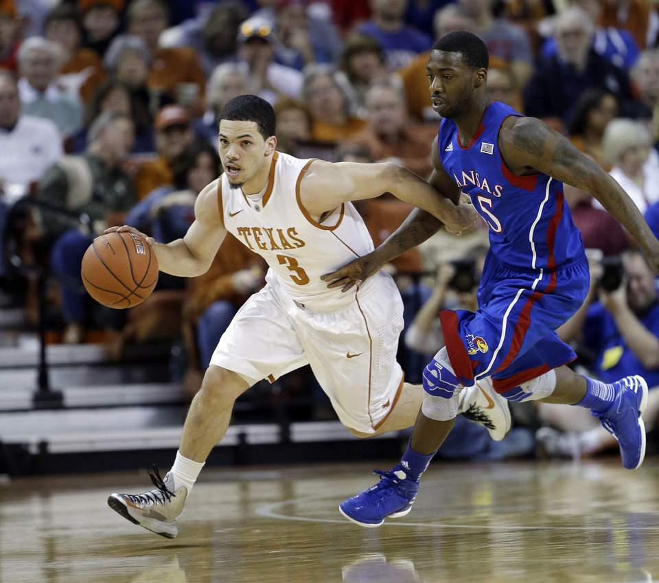 Texas' Javan Felix (3) drives the ball past Kansas' Elijah Johnson, right, during the first half of an NCAA college basketball game, Saturday, Jan. 19, 2013, in Austin, Texas. (AP Photo/Eric Gay)