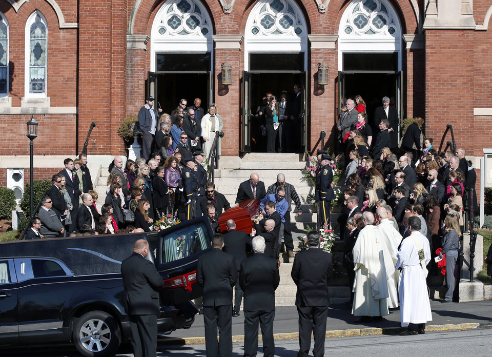 Photo - Mourners line the steps of St. Augustine Church in Andover, Mass., Monday Oct. 28, 2013, as the casket of slain Danvers High School teacher Colleen Ritzer is carried out from her funeral Mass into a hearse. Ritzer, 24, who taught math at Danvers High School, was killed in a school bathroom after dismissal on Oct. 22, police said. Her body was found in woods behind the school. Philip Chism, 14, has pleaded not guilty to a murder charge. (AP Photo/Elise Amendola)