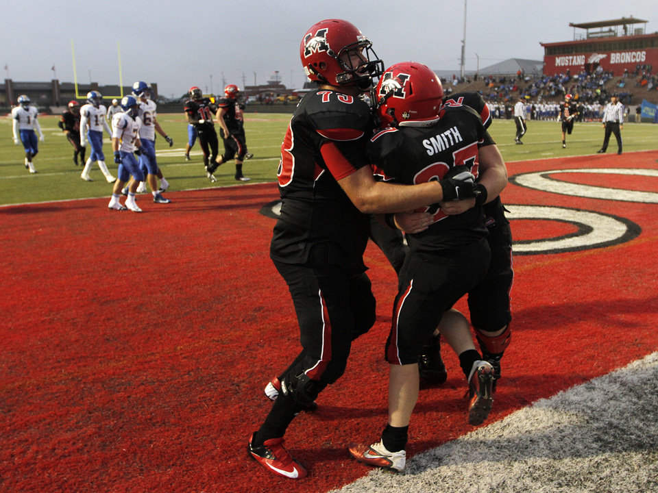 Photo - Mustang's Dakota Warrington (12), Cutter Smith (37), and Tristan Hill (73) celebrate after a touchdown during a high school football game between Mustang and Stillwater in Mustang, Okla., Friday, Sept. 14, 2012.  Photo by Garett Fisbeck, The Oklahoman
