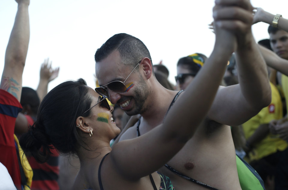 Photo - In this July 4, 2014, photo, A Brazilian woman and a Colombian man dance during the World Cup Fan Fest 2014 on Copacabana beach, in Rio de Janeiro, Brazil. Brazilian women say foreign male fans have behaved well, and have displayed a more enlightened, less macho attitude than that of Brazilian guys. (AP Photo/Silvia Izquierdo)
