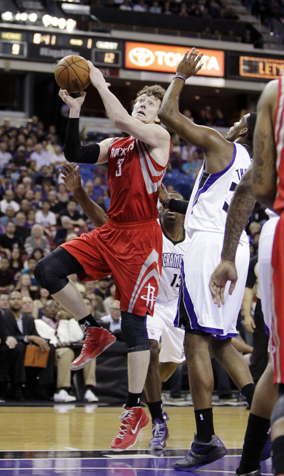 Photo - Houston Rockets center Omer Asik, left, of Turkey, drives against Sacramento Kings forward Jason Thompson during the first quarter of an NBA basketball game in Sacramento, Calif., Wednesday, April 3, 2013. (AP Photo/Rich Pedroncelli)