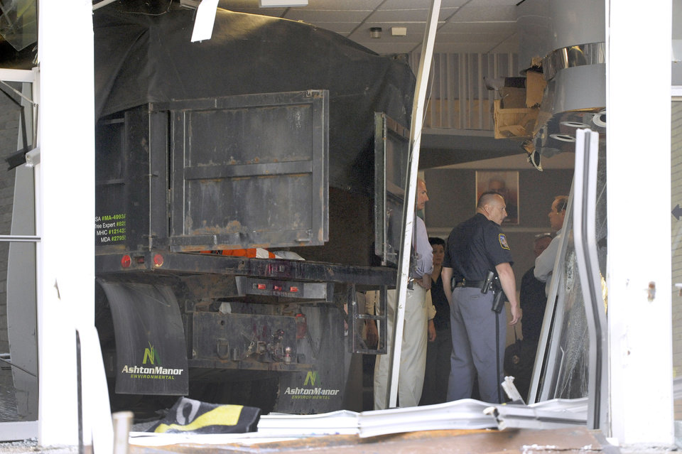 Photo - Police and WMAR-TV officials inspect damage caused by a vehicle that crashed into the television station's building Tuesday, May 13, 2014, in Towson, Md. Officials announced that a man was taken into custody after allegedly crashing the vehicle into the building. (AP Photo/Steve Ruark)