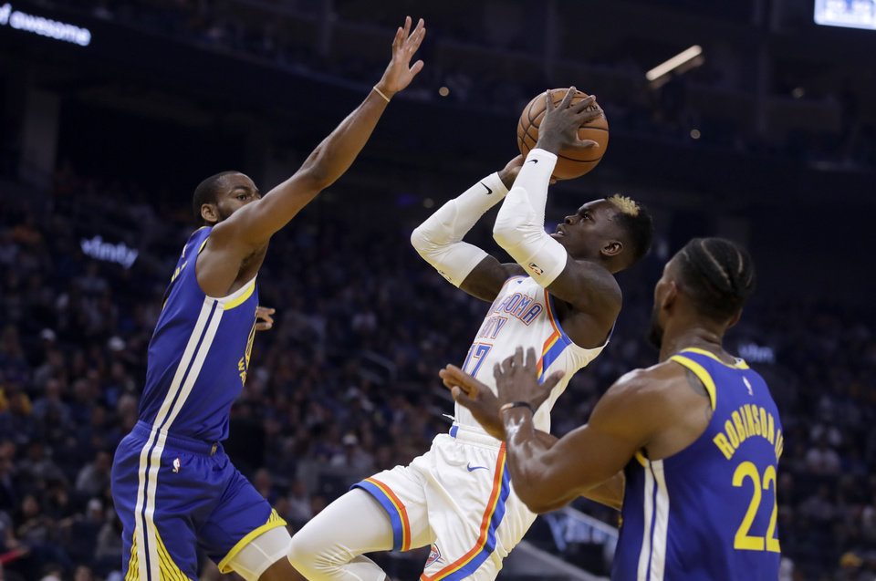 Photo - Oklahoma City Thunder guard Dennis Schroder, center, shoots between Golden State Warriors' Alec Burks, left, and Glenn Robinson III (22) in the first half of an NBA basketball game Monday, Nov. 25, 2019, in San Francisco. (AP Photo/Ben Margot)