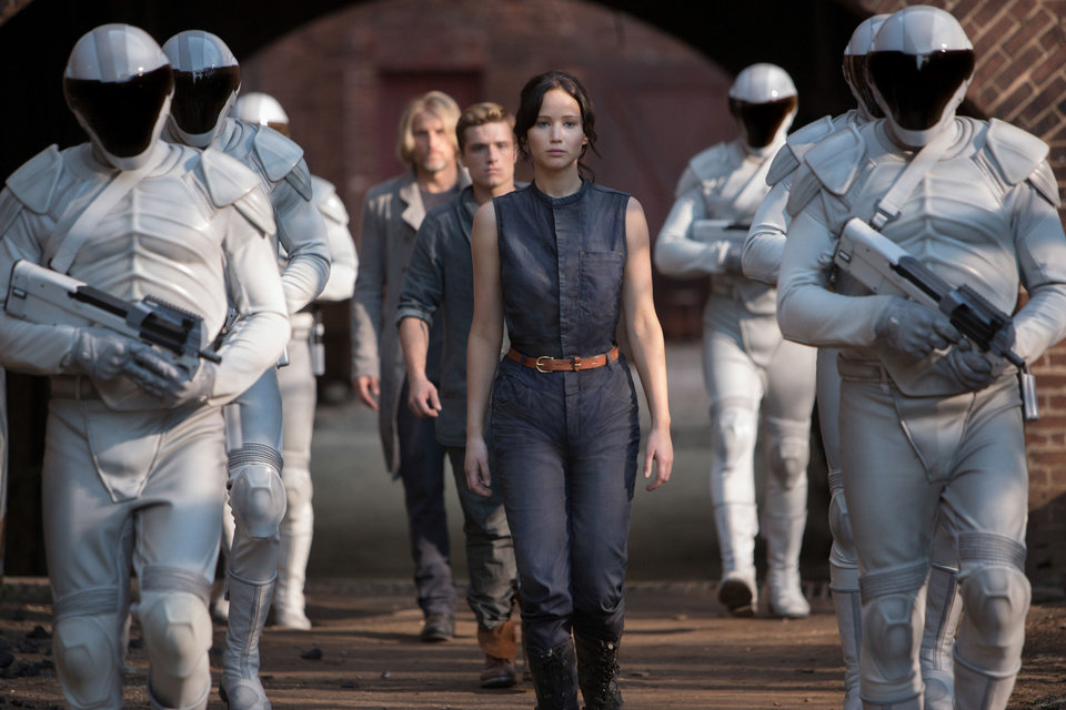 Photo - This image released by Lionsgate shows Jennifer Lawrence as Katniss Everdeen, from foreground to background, Josh Hutcherson as Peeta Mellark and Woody Harrelson as Haymitch Abernathy in a scene from