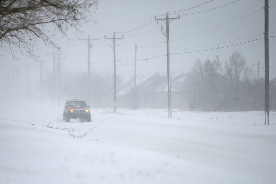 Photo - A vehicle travesl east on NW 164 in northwest Oklahoma City during a winter storm, Sunday, Feb. 14, 2021. [Bryan Terry/The Oklahoman]