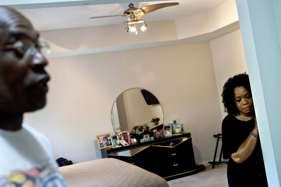 Photo -   Michael, left, and Patricia Jackson stand in their bedroom after sifting through bank documents in their home Saturday, June 16, 2012, in Marietta, Ga. On a suburban cul-de-sac northwest of Atlanta, the Jacksons are struggling to keep a house worth $100,000 less than they owe. Their voices and those of many others tell the story of a country that, for all the economic turmoil of the past few years, continues to believe things will get better. But until it does, families are trying to hang on to what they've got left. The Great Recession claimed nearly 40 percent of Americans' wealth, the Federal Reserve reported last week. The new figures, showing Americans' net worth has plunged back to what it was in 1992, left economists shuddering. (AP Photo/David Goldman)