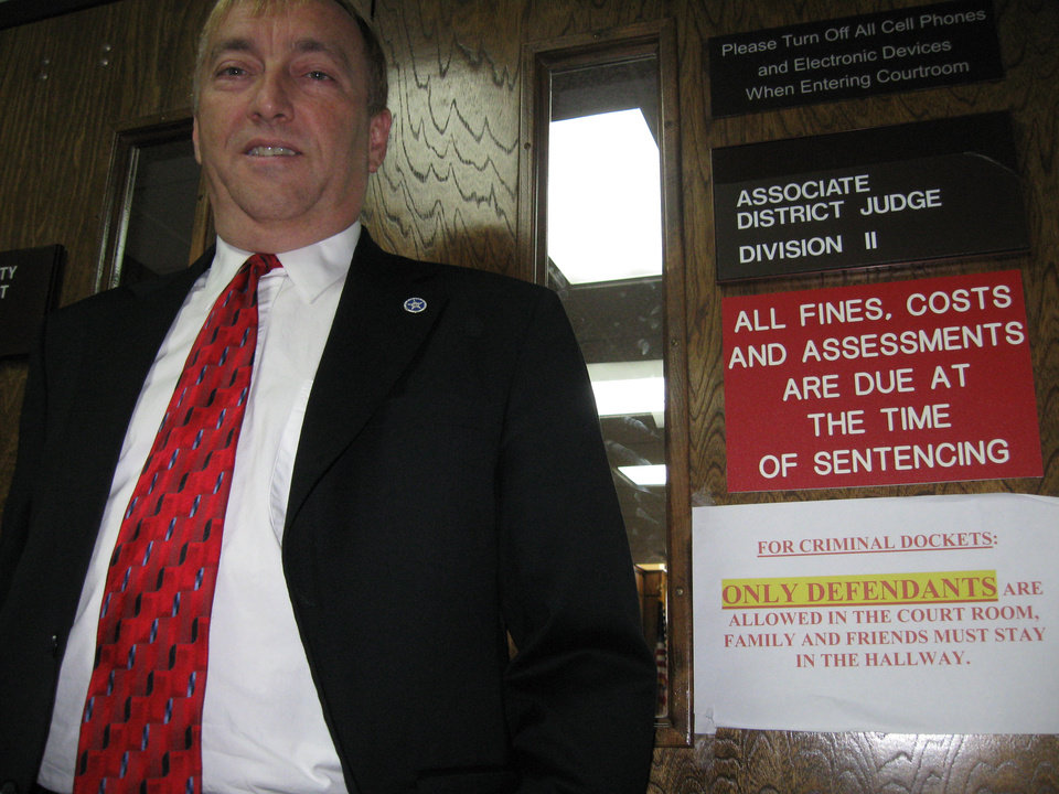 Photo - David Starkey stands next to a sign on District Judge Dwayne Steidley's courtroom in Rogers County that says the public isn't welcome.  PHOTO BY TONY THORNTON,  THE OKLAHOMAN