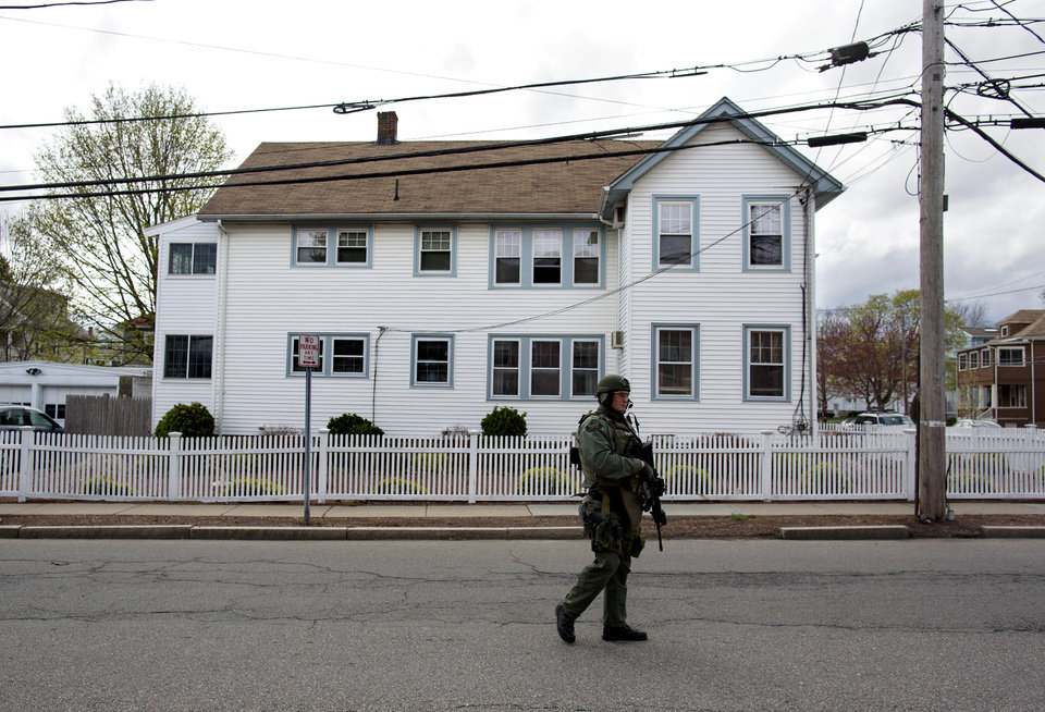 A heavily armed police officer walks along a street during house to house searches in the neighborhoods of Watertown, Mass. Friday, April 19, 2013, as a massive search continued for one of two suspects in the Boston Marathon bombing. A second suspect died in the early morning hours after an encounter with law enforcement. (AP Photo/Craig Ruttle) ORG XMIT: MACC117