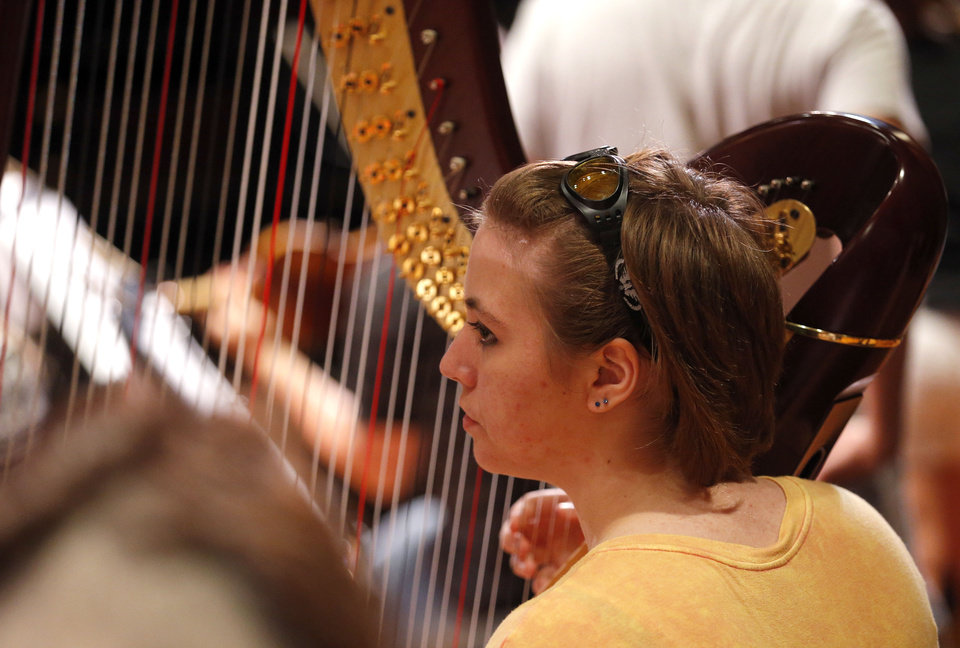 Photo - Olivia Wilson of Edmond plays the harp during orchestra practice during the Oklahoma Summer Arts Institute at Quartz Mountain Arts and Conference Center near Lone Wolf on Monday, June 17, 2013. PHOTO BY SARAH PHIPPS, The Oklahoman  SARAH PHIPPS