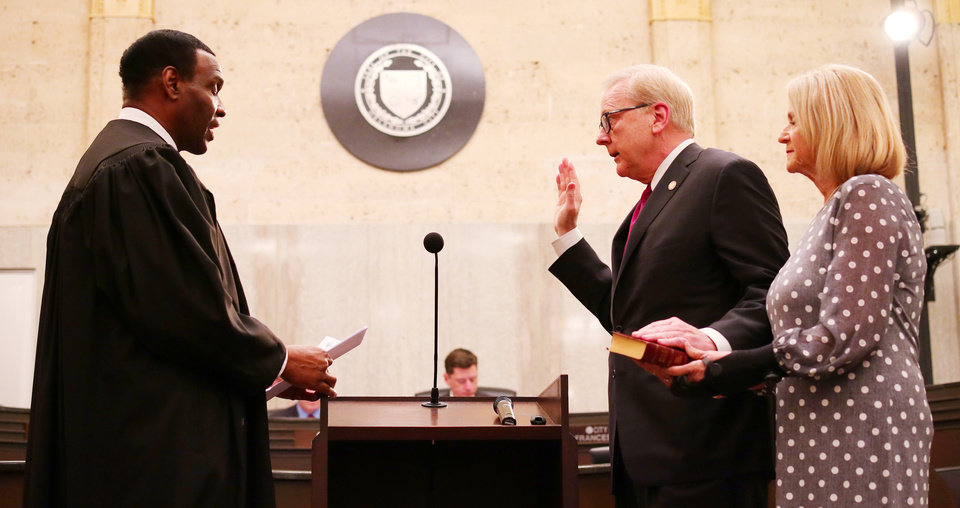Photo - Municipal Judge Donald Kiffin adminisiters the oath to David Greenwell, ward 5, with his wife, Pam, during the swearing in ceremony for the Oklahoma City Council, Tuesday, April 9, 2019.  Photo by Doug Hoke/The Oklahoman