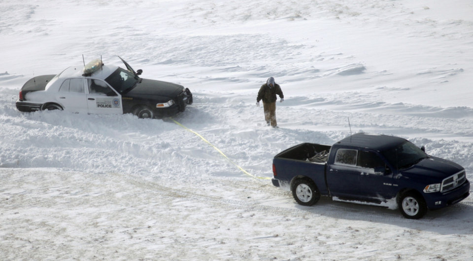 A pickup hooks up a tow strap to free an Oklahoma City police car that was stuck in a drift along the access road of I-235 near Britton Road during a major winter storm that hit central Oklahoma Tuesday, Feb. 1, 2011. Photo by Doug Hoke, The Oklahoman