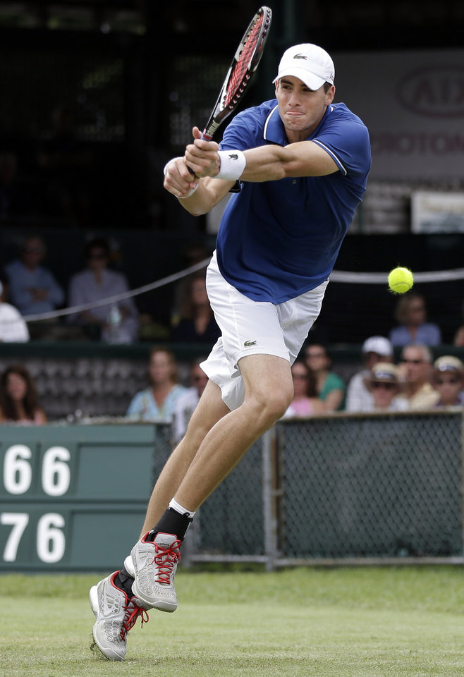 Photo - John Isner of the USA reurns to opponent Ivo Karlovic of Croatia during a quarterfinal match at the Hall of Fame Tennis Championships in Newport, R.I. Friday, July 12, 2013. Isner won 7-6 (3), 7-6 (3). (AP Photo/Elise Amendola)