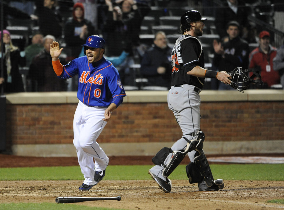 Photo - New York Mets' Omar Quintanilla (0) celebrates as he crosses home plate behind Miami Marlins catcher Jarrod Saltalamacchia (39) to score the winning run on Curtis Granderson's single in the ninth inning of a baseball game at Citi Field on Friday, April 25, 2014, in New York. The Mets won 4-3. (AP Photo/Kathy Kmonicek)