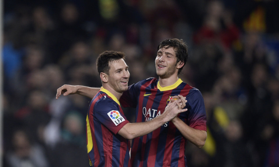 Photo - FC Barcelona's Lionel Messi, from Argentina, left, reacts after scoring with his teammate Sergio Roberto against Getafe during a Copa del Rey soccer match at the Camp Nou stadium in Barcelona, Spain, Wednesday, Jan. 8, 2014. (AP Photo/Manu Fernandez)